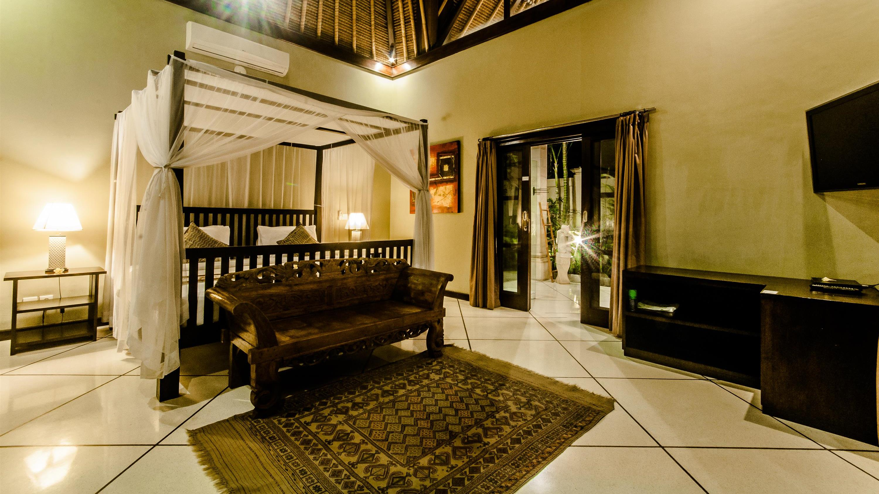 Bedroom with Sofa and TV at Night - Villa Kebun - Seminyak, Bali
